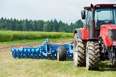 stock photo of plowed field  - Ploughing heavy tractor during cultivation agriculture works at field with plough - JPG