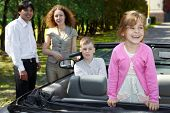 Little girl stands on backseat in cabriolet and laughs, parents stand near car