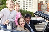Family of four in cabriolet, children stand on backseats, parents sit on front seats, everybody laug