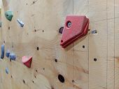 Closeup Of Red And Colorful Climbing Pieces On A Wall In A Gym For Climbing Exercise Both For Leisur poster