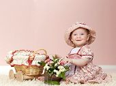 little child baby girl playing with flowers indoors in baby room on the floor on the carpet smiling