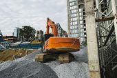 Large Orange Excavator Working On A Gravel On Construction Site. Details Of Industrial Excavator. Bi poster