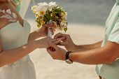 Closeup Of A Couple Exchanging Wedding Rings During A Wedding Ceremony On The Beach. Wedding And Hon poster