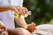 Closeup of masseuse hands pouring aroma oil on woman back. Woman prepare to do oriental spa massage  poster