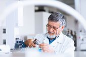 stock photo of chromatography  - senior male researcher carrying out scientific research in a lab using a gas chromatograph  - JPG