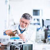 senior male researcher carrying out scientific research in a lab using a gas chromatograph (shallow DOF; color toned image)