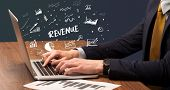 Businessman working on laptop with REVENUE inscription, modern business concept poster