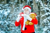 Winter Time. Merry Christmas And Happy Holidays. Santa Claus Blowing Magic Snow Of His Hands. Photo  poster