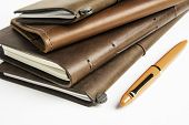 A Stack Of Leather-bound Travel Writing Journals With An Orange Fountain Pen Set On Plain White Back poster