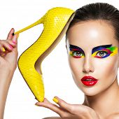 beautiful face of  woman with vivid make-up of eyes holds the yellow high heel. Fashion concept. poster