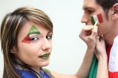 Italian football fans putting on facepaint