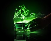 picture of absinthe  - Hand holding one of two glasses of burning green absinth - JPG