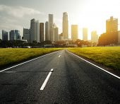 Asphalt road leading to a city with tall buildings through green meadow