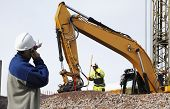 stock photo of earth-mover  - bulldozer and industrial workers in action - JPG