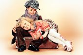 image of charming  - Cute little boy is sitting on the old suitcase with charming little lady - JPG