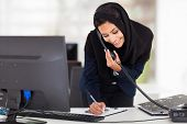 stock photo of hijabs  - happy young middle eastern businesswoman working in office - JPG