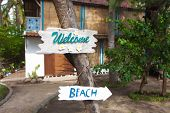 Wooden welcome sign in front of house and direction to beach