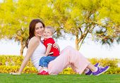 Mother with cute baby boy sitting down on green grass in spring park, mom with son enjoying springtime nature, happy family spending time outdoors