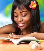 Beautiful African woman reading book on the beach, pretty black female enjoying summer vacation rela