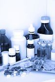 Medical bottles and pills in blue light