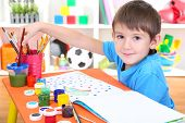 stock photo of diligent  - Cute little boy painting in his album - JPG