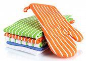 Orange potholder and stack of kitchen towels isolated on white