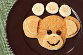Fun kid's breakfast of a smiling monkey face with chocolate chips for eyes on plate with banana slic