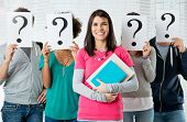 Woman Standing In Front Of Friends Holding Paper With Question Mark Signs