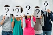 stock photo of placard  - Students Hiding There Face With Question Mark Sign - JPG