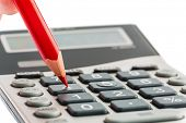 a red pen on a calculator. save on costs, expenditures and budget for bad economy