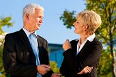 Business people - mature or senior - standing in a park outdoors talking
