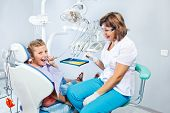 pic of pediatrics  - Kid playing with dental drill during  her first pediatric dentist visit - JPG
