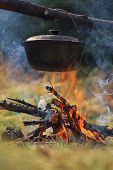 Cooking in the mountains. Cauldron on fire