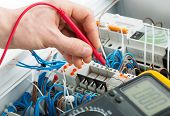 stock photo of fuse-box  - Hand of an electrician with multimeter probe at an electrical switchgear cabinet - JPG