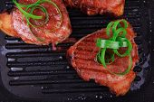 roast bloody beef fillet steaks on black teflon grill plate with green leaves  isolated on white bac