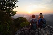 Hikers with backpacks relaxing on top of a mountain and enjoying sunrise