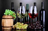 Variedade de vinho em copos e garrafas sobre fundo cinza
