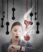 Businesswoman realising the late time from smoking watch with hanging phones around her