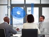 Smiling business people using blue pie chart on futuristic interface in a meeting
