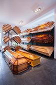 stock photo of funeral home  - Wooden brown different coffins in funeral home - JPG