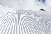 Fresh snow groomer tracks on a ski piste