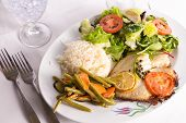 Tilapia Cooked With Capers Lemon And Tomatoes Served With Vegetables And Pilaf Rice