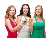 party, celebration, friends, bachelorette party, birthday concept - three beautiful women in evening dresses with cocktails