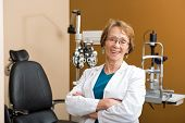 Portrait of happy senior female optometrist with arms crossed in optician store