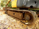 picture of caterpillar  - Caterpillar tracks of an excavator covered in mud by the wet conditions - JPG