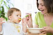 Joyous mother feeding cute messy baby boy with vegetable puree.