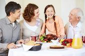 Portrait of happy family sitting at festive table and looking at joyful girl during Thanksgiving dinner