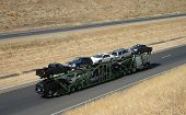 stock photo of car carrier  - a large truck delivers new cars via highway - JPG
