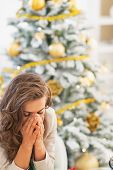 Stressed Young Woman Sitting In Front Of Christmas Tree