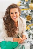 Portrait Of Happy Young Woman Signing Card On Christmas Present Box